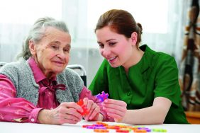 carer with puzzle xxl Green 282x188 - Care Homes Dorset & Residential Care Wiltshire